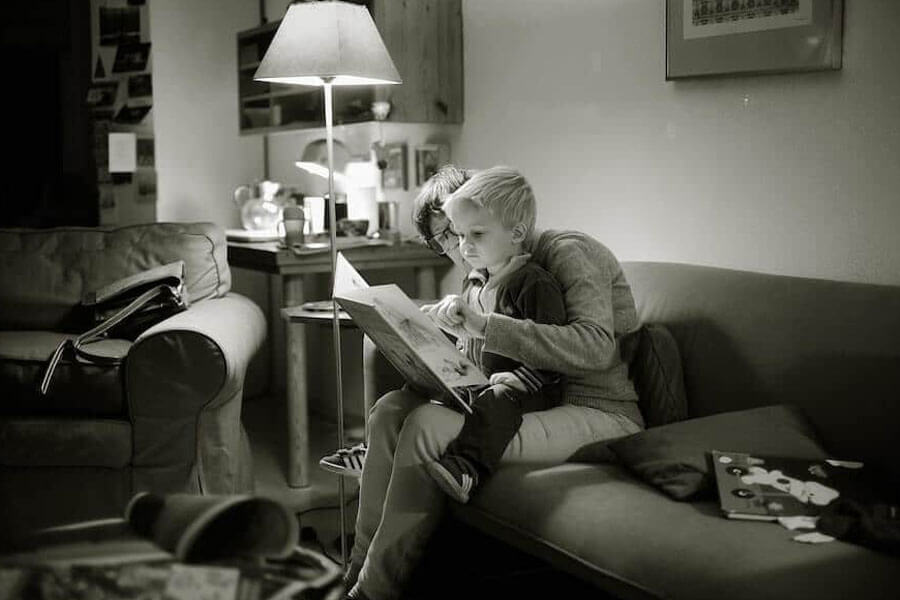 Young boy sitting on his mums lap reading a book