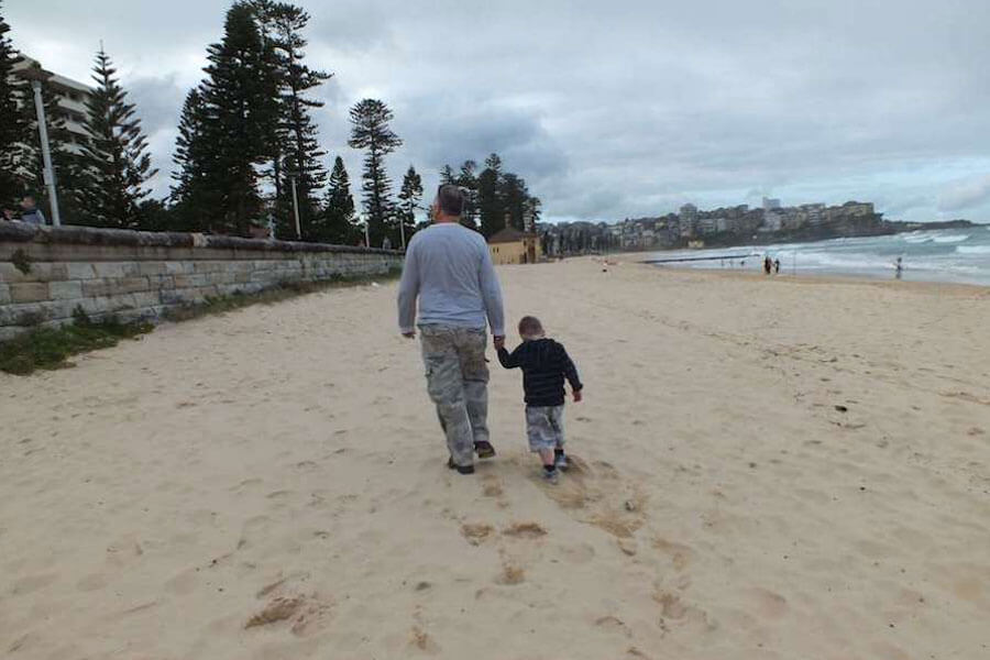 Boy walking on beach with his dad