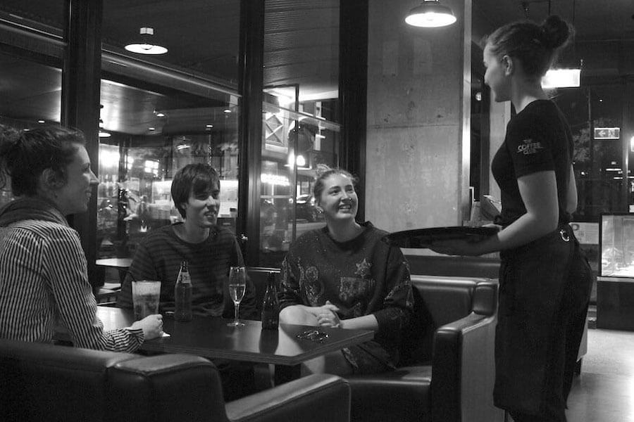 Three young adults in a restaurant ordering meal with waitress