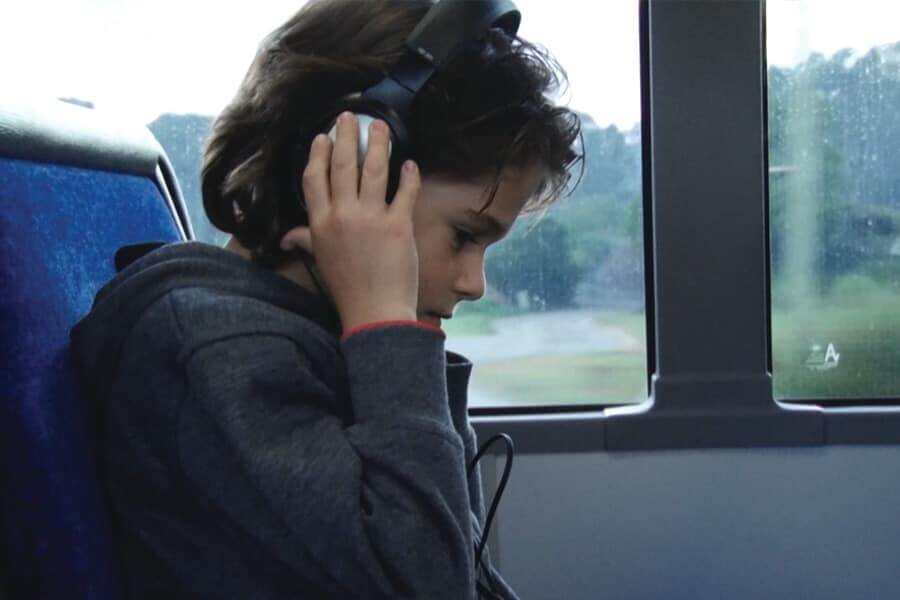 Boy with headphones on and hands up holding the headphones
