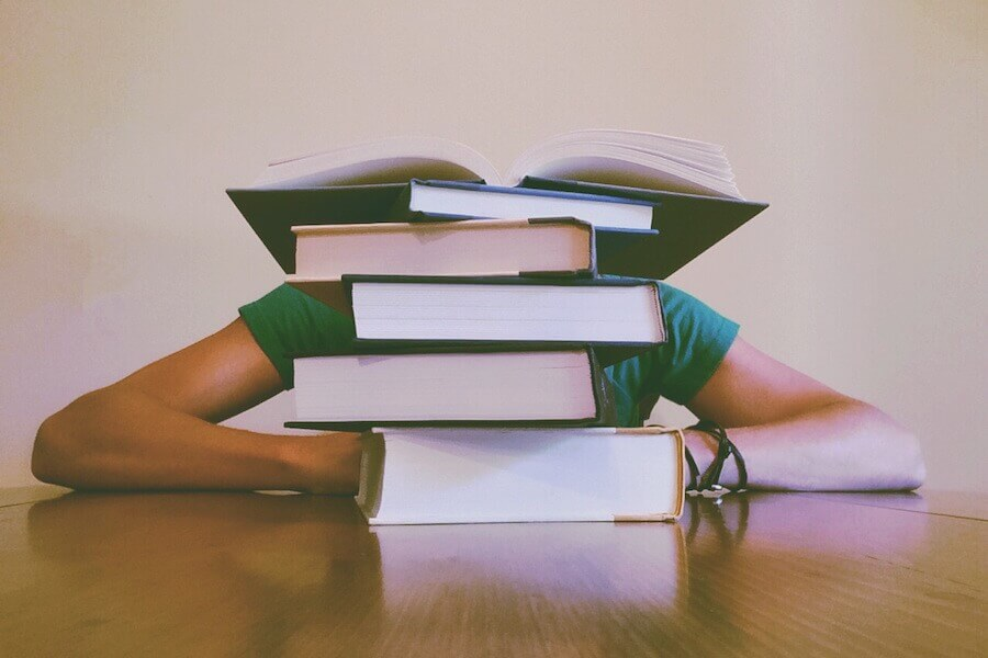 Pile of books on a desk with person behind them with their head on the desk