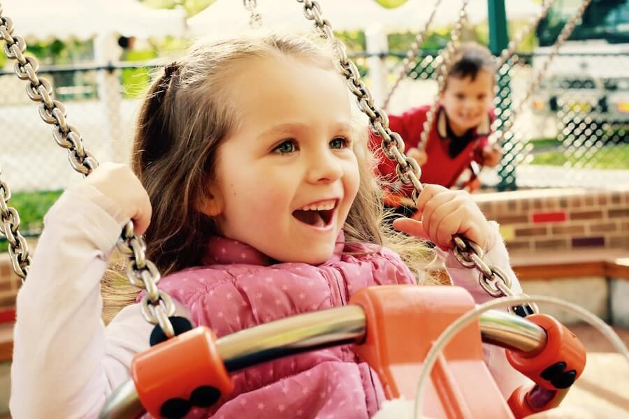 Small girl laughing on a swing