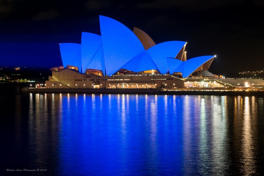 Sydney opera house lit up in blue lights at night