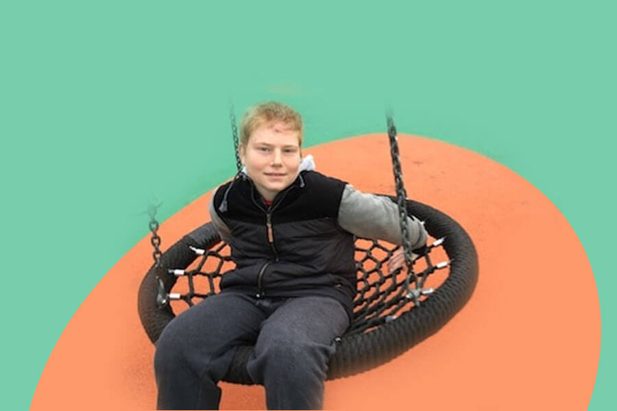 Adam Stewart a teenager with autism sitting on a swing