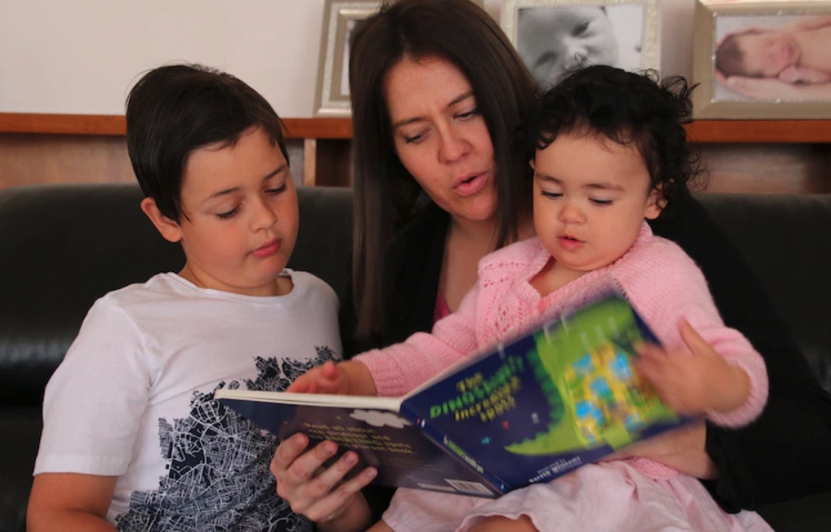 mother with son and daughter reading a book