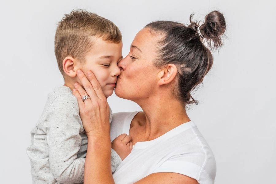 mother kissing autistic son