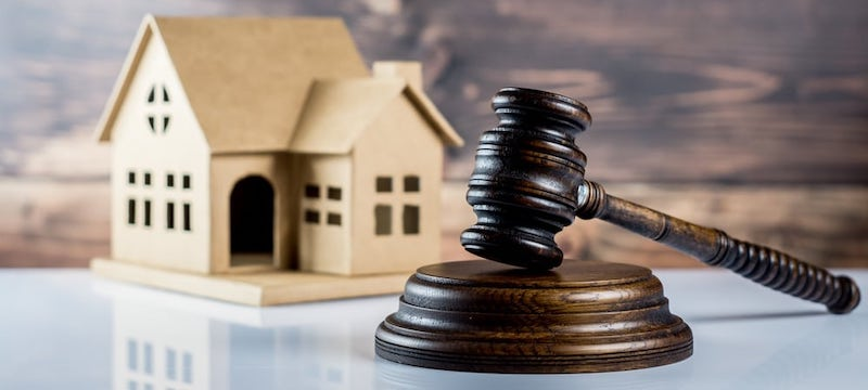 Property Auctions: Image of an auction gavel in front of a model house