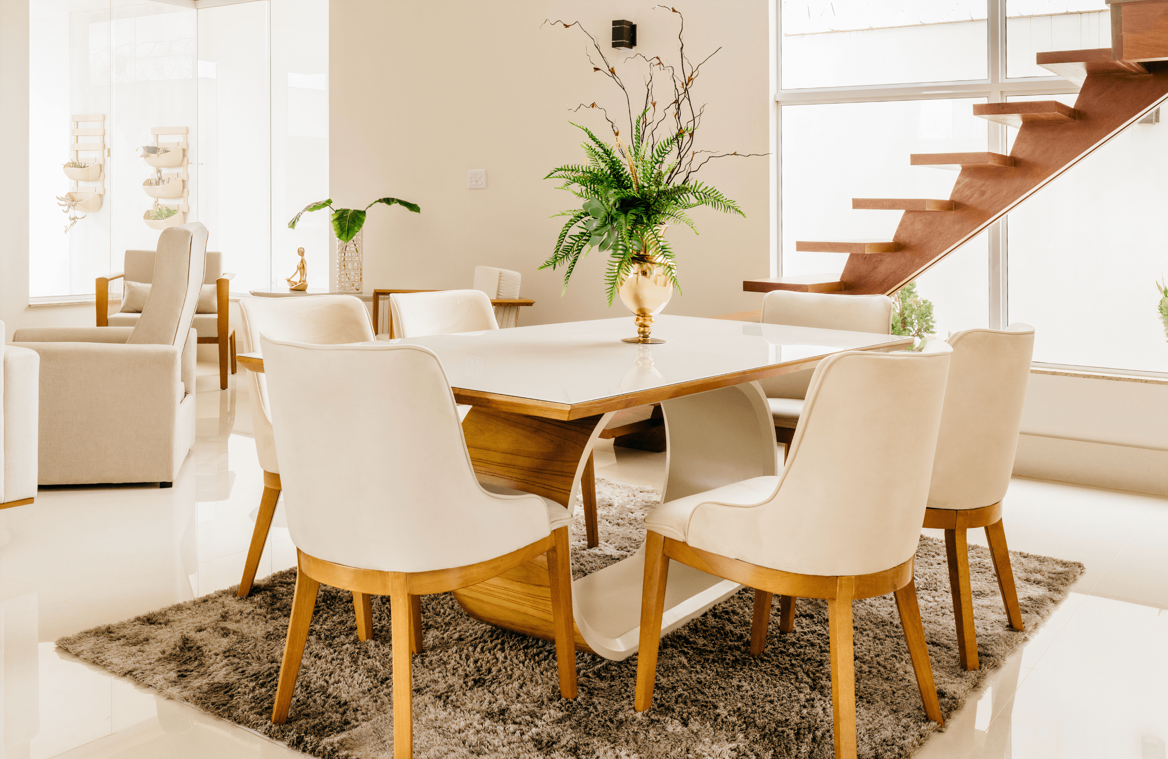 An image of a wooden dining room table with a white glass top, with white chairs surrounding it and a plant as the centerpiece.