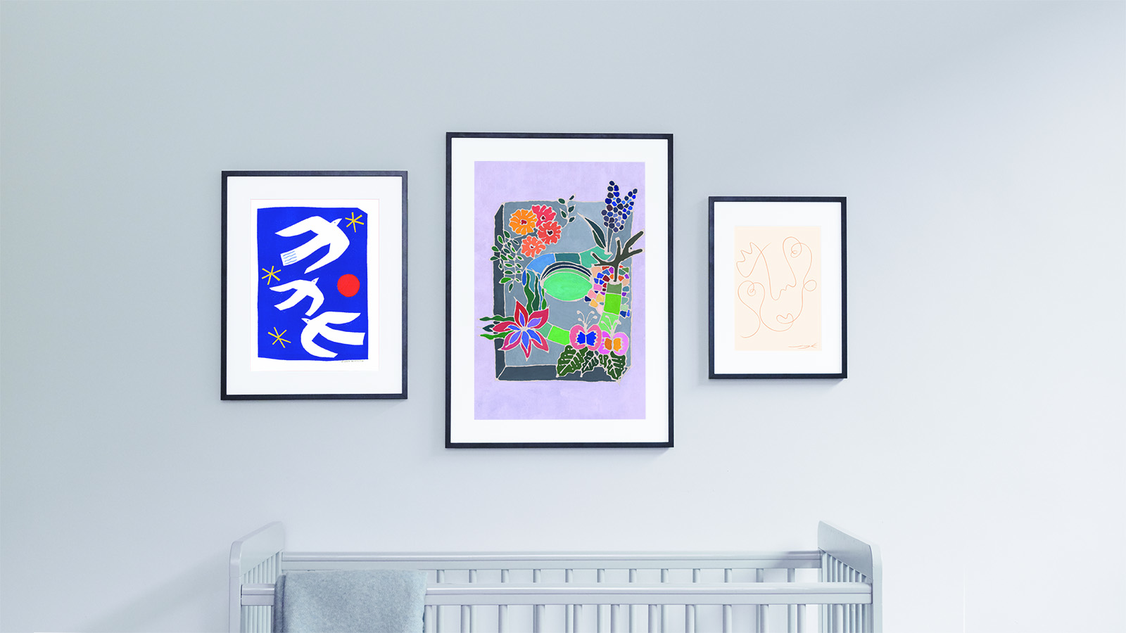 Triptych of artworks in various sizes above a cot. On the left is Sophie Harding's 'Follow Your Dreams' in A3, in the middle is Sophia Niazi's 'Cereal Box Garden' in A2, and on the right is Jessica Yolanda Kaye's A4