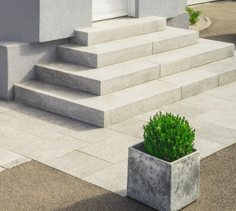 Stone stair near a stone cabinet with plant.