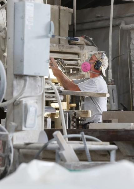 Man in the respirator is making custom stone cutting.