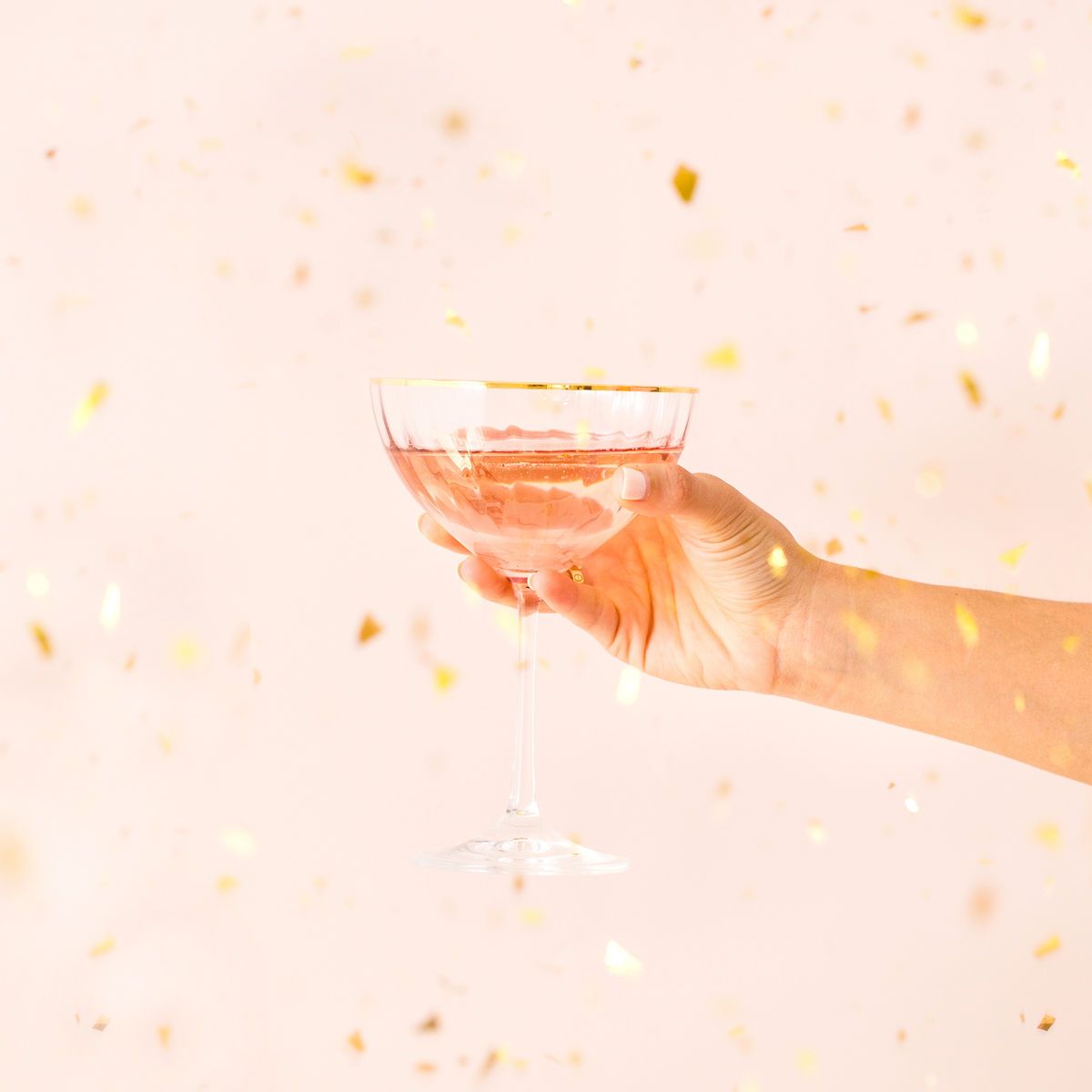 Hand holding a champaign glass to cheers.
