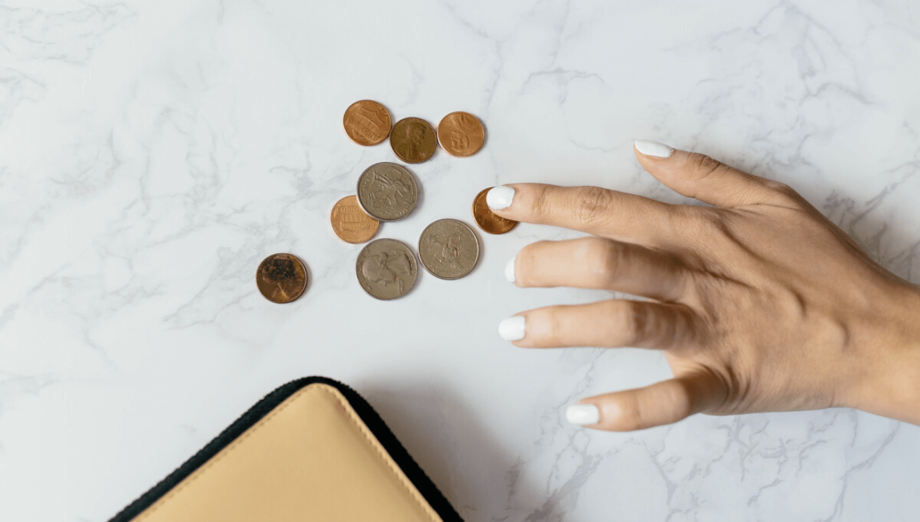 Wallet with coins on desk. A hand counting the coins.