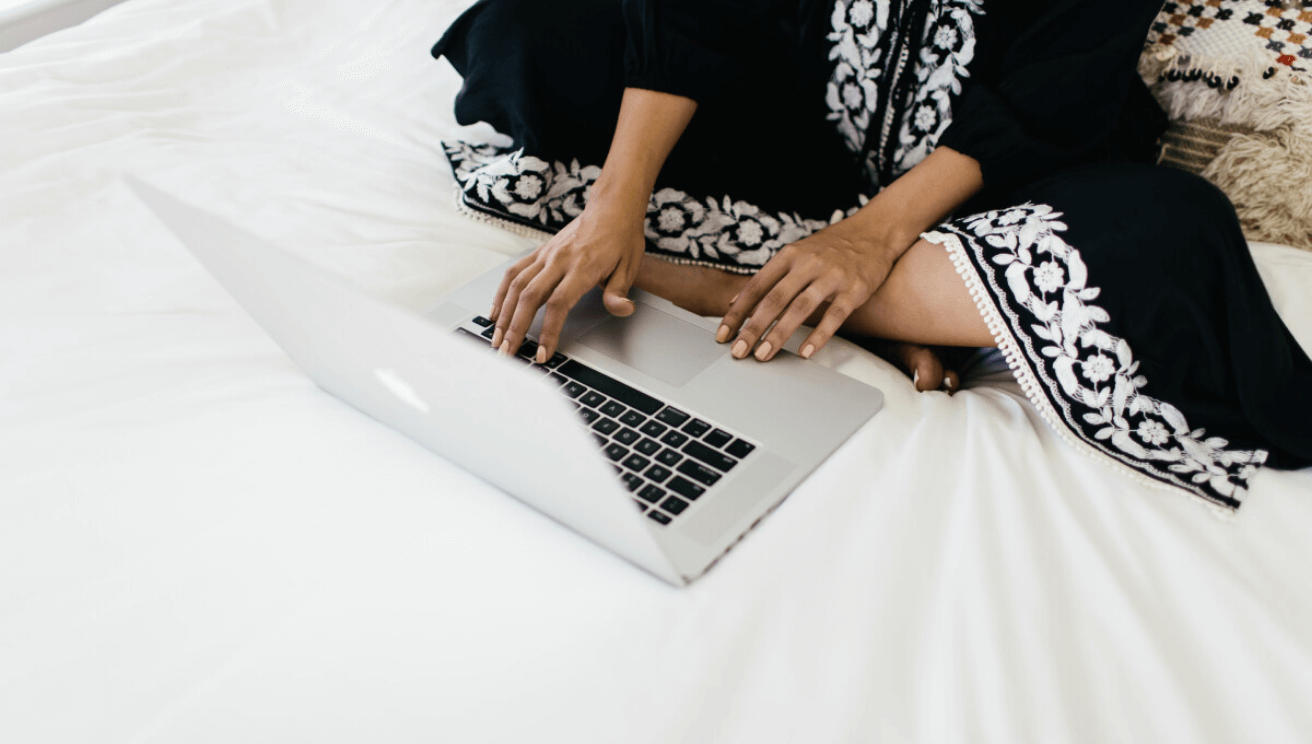 Woman sitting on a bed working on her computer