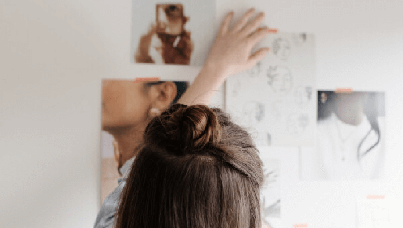 Woman creating a mood board against a wall