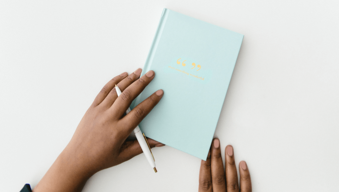 Hand holding pencil and notebook