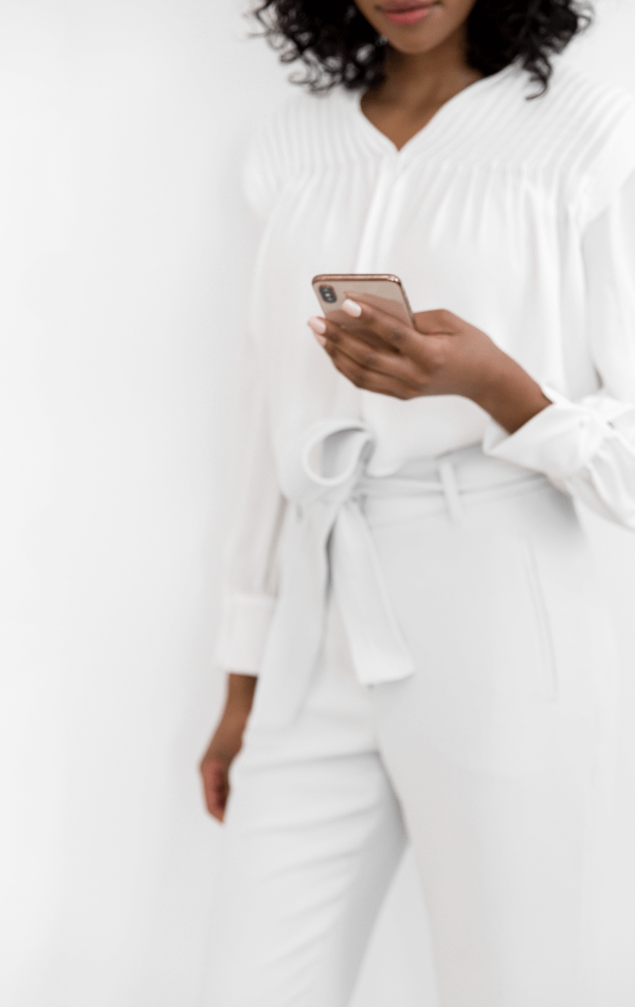 Woman leaning against a wall looking at her phone