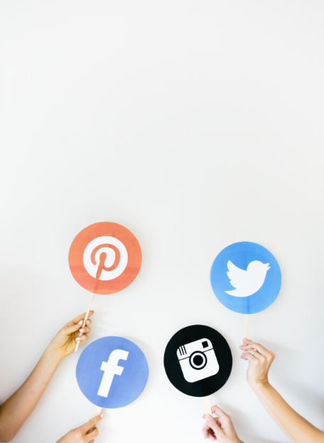 Hands holding sign with social media icons on them