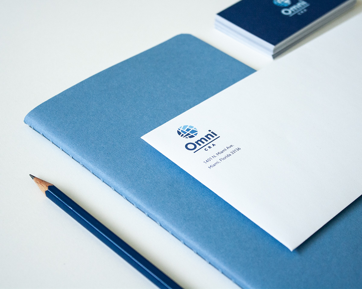 Omni CRA envelope and business card with stationery items