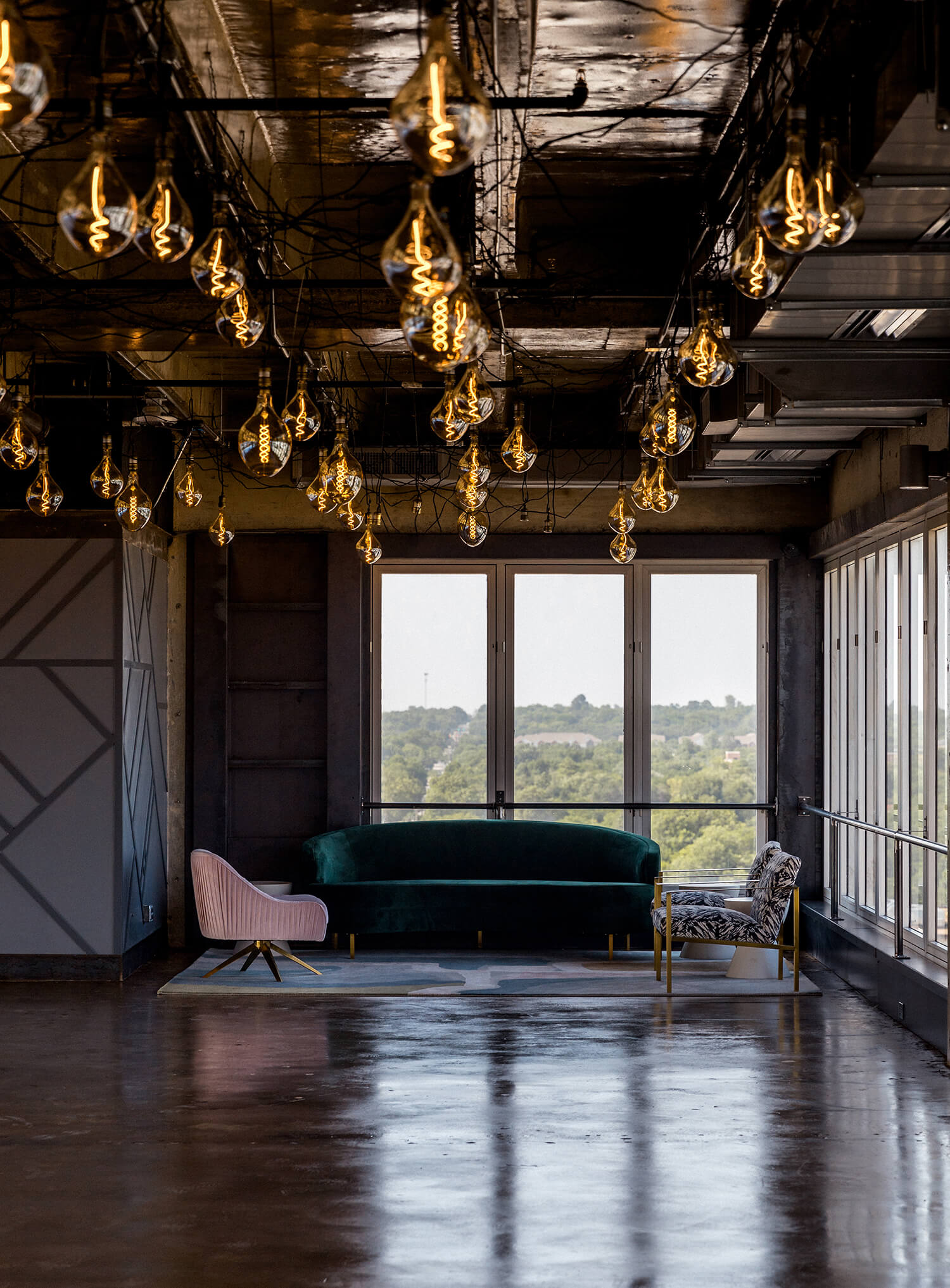 The lounge area of Sunago Bell event venue featuring posh, modern chairs and a couch, tucked away under twinkling Edison bulbs.