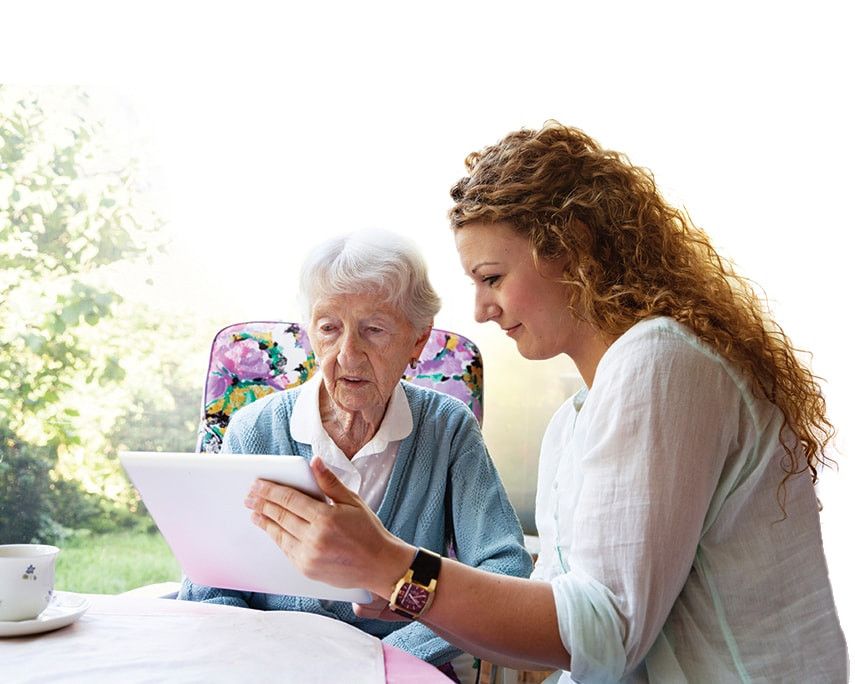 Caretaker from retireinplace helps an elderly woman with her legal information on a tablet