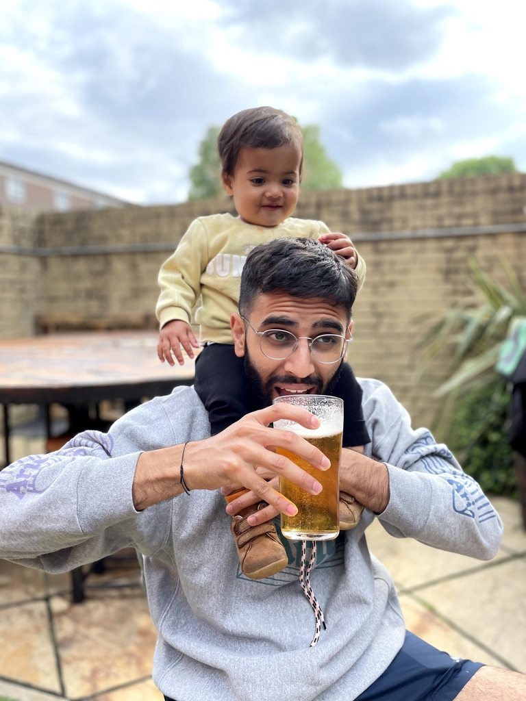 A fun photo of me drinking beer with my daughter on my shoulders.