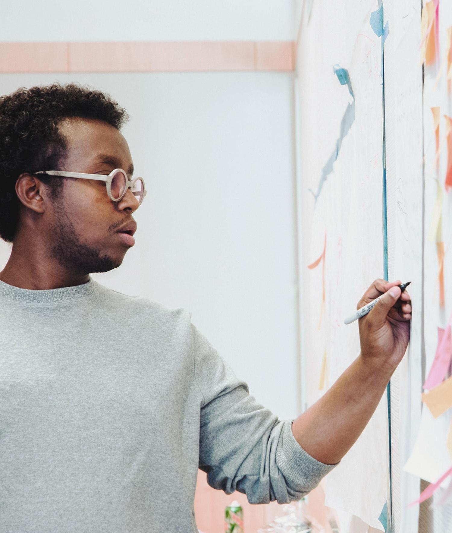 Man writing down business plan on whiteboard