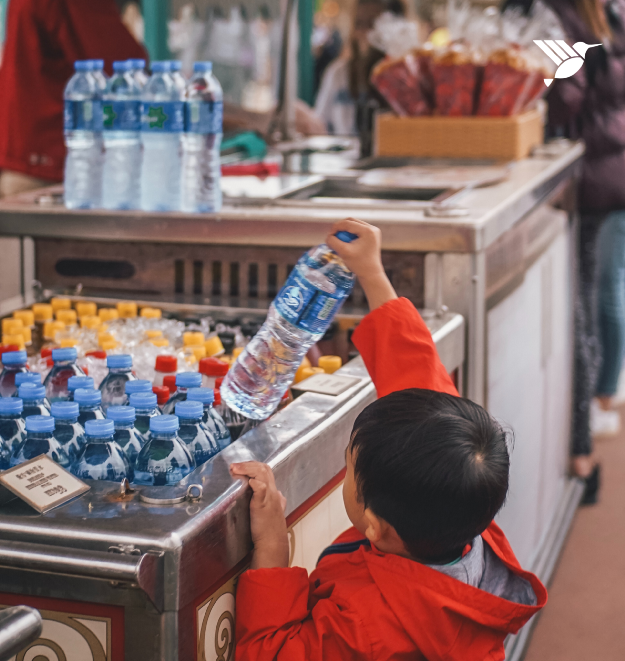 A child grabbing a plastic water bottle
