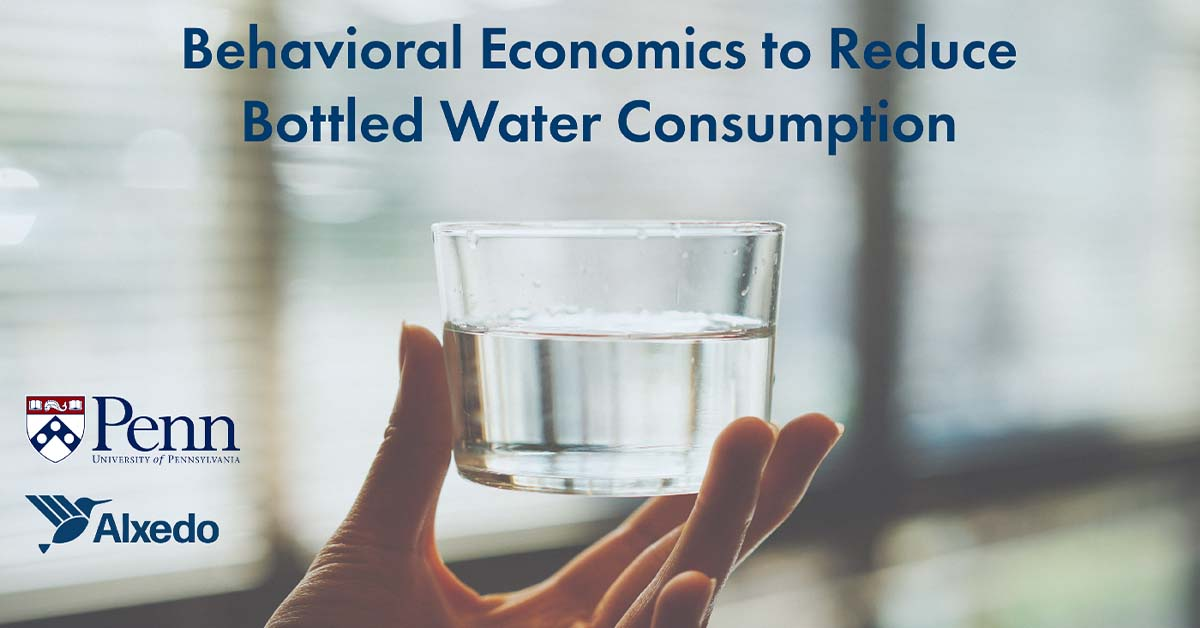 """A glass of water being hold in the hand with a text above it saying: """"Behavioral economics to reduce bottled water consumption"""""""