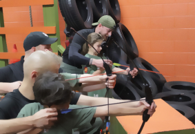 trainer teaches children to shoot a bow