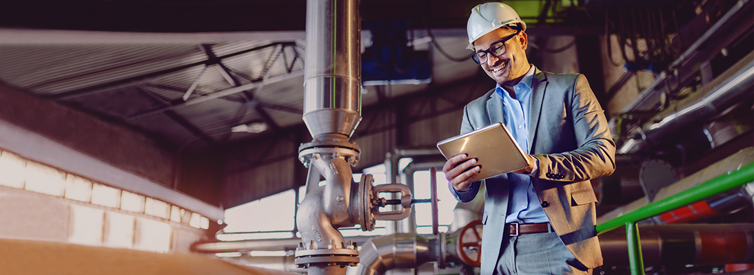 Man in suit looking at a tablet in a factory building