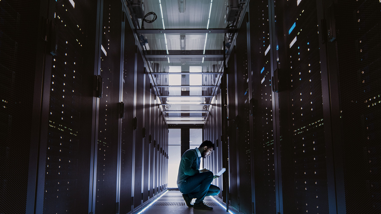 Man kneels in the server room and checks a system copy on the laptop