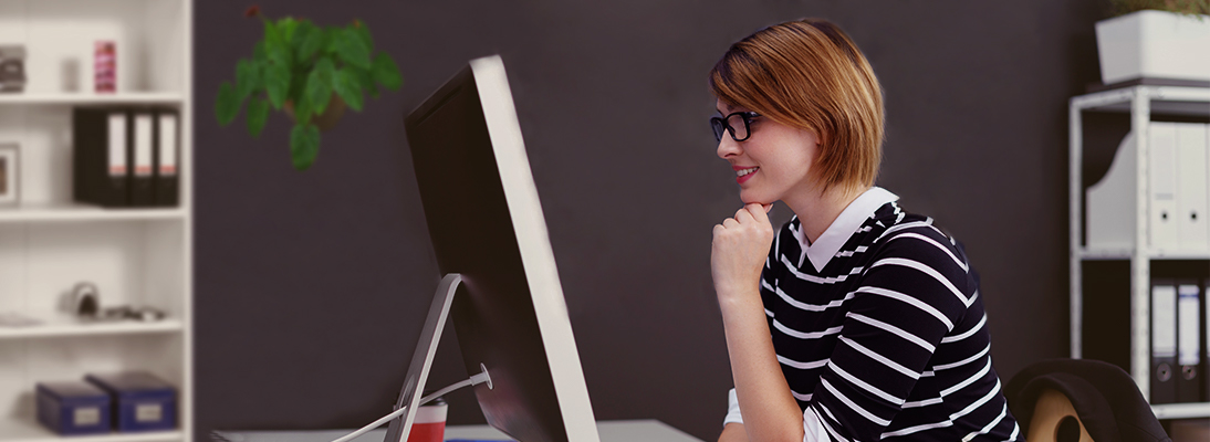 Young woman sitting in front of a screen with user interface by Libelle DataMasking