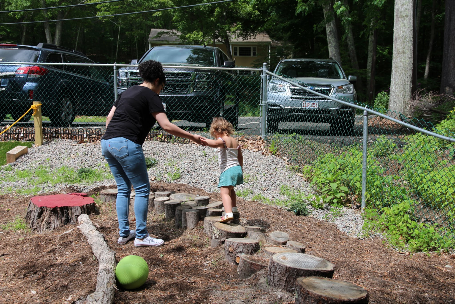 A teacher and student playing in the natural playground at StoryHeights Montessori Norfolk Location.