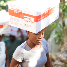 Woman carrying box of Medika Mamba product on head