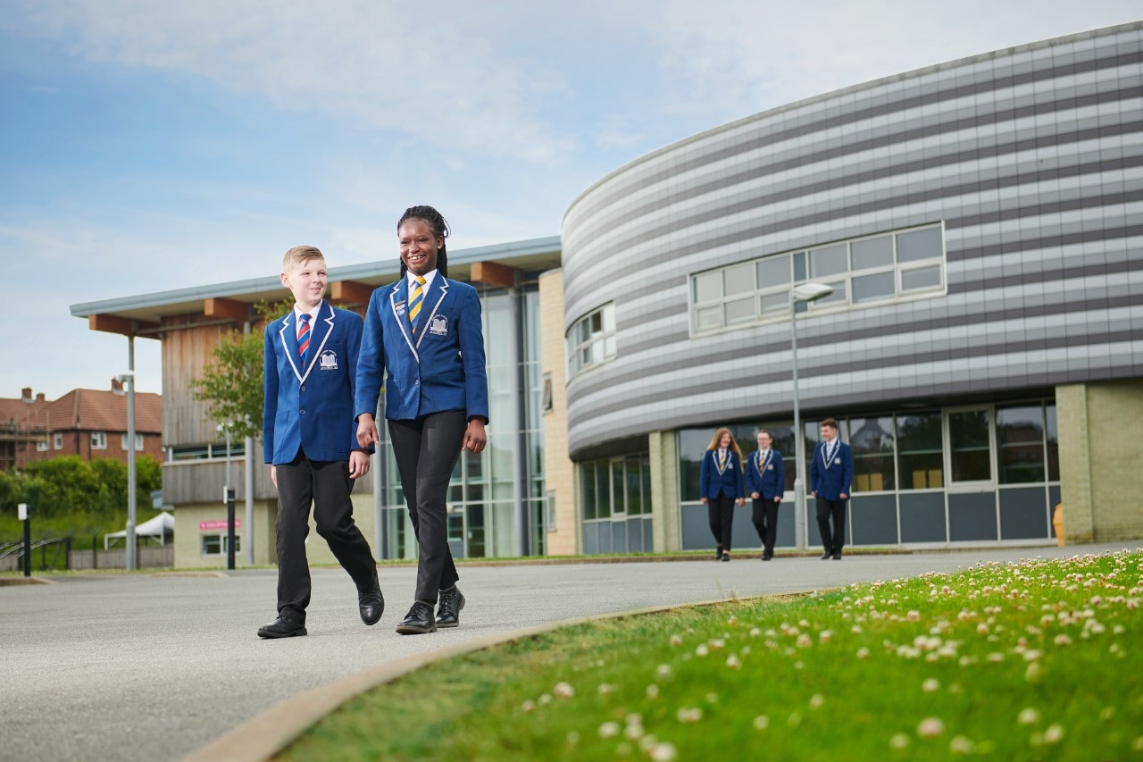 Academy 360 pupils, boy and girl, walking near the school building