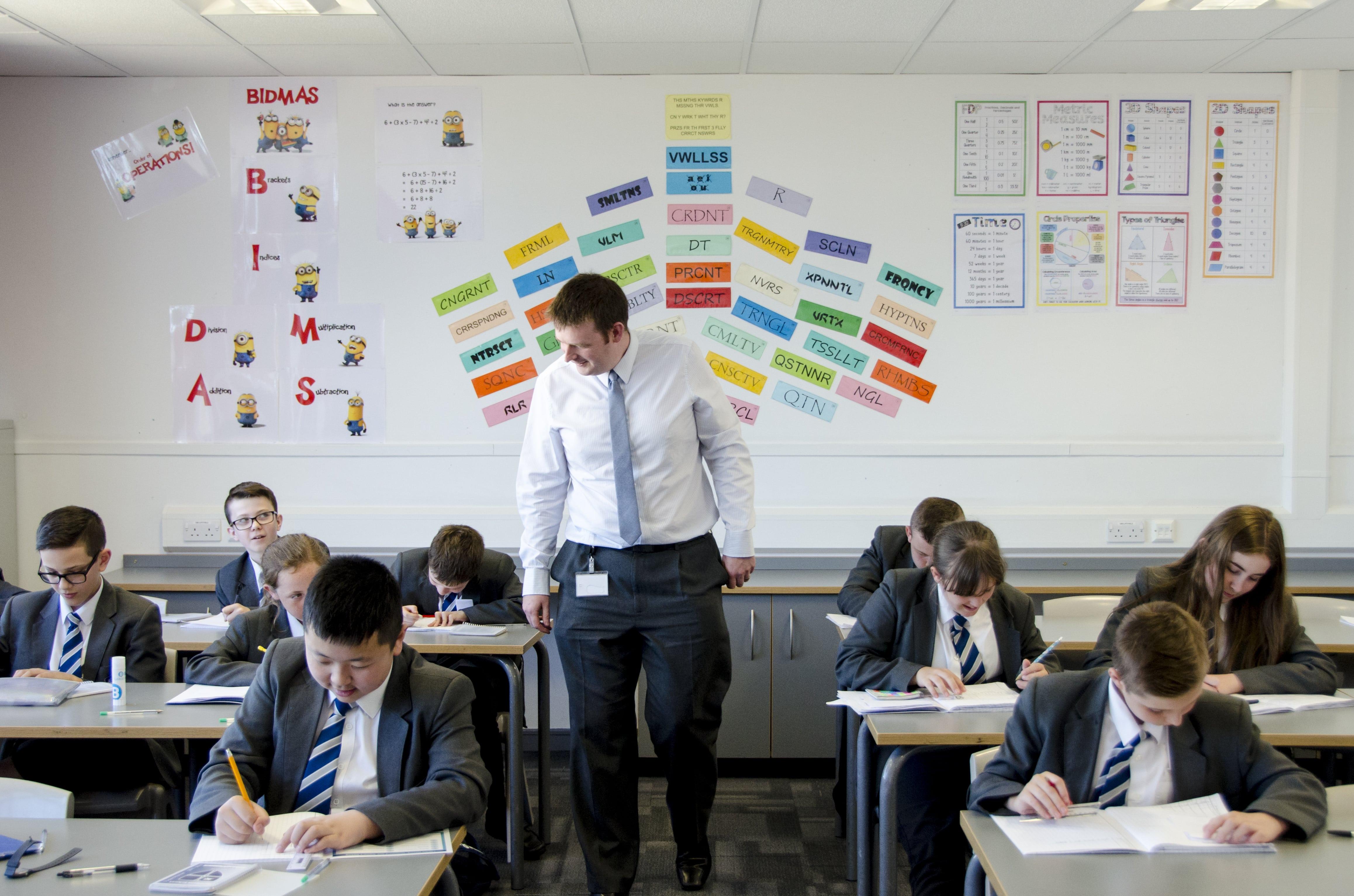School teacher looking over pupils' work during class