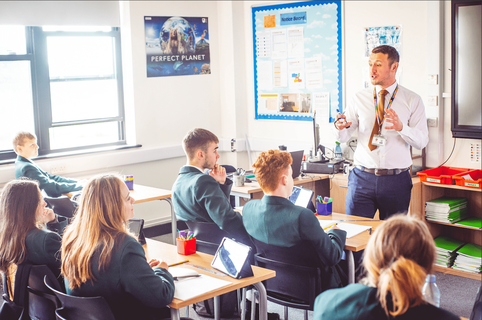 A teacher talking to a class full of students.