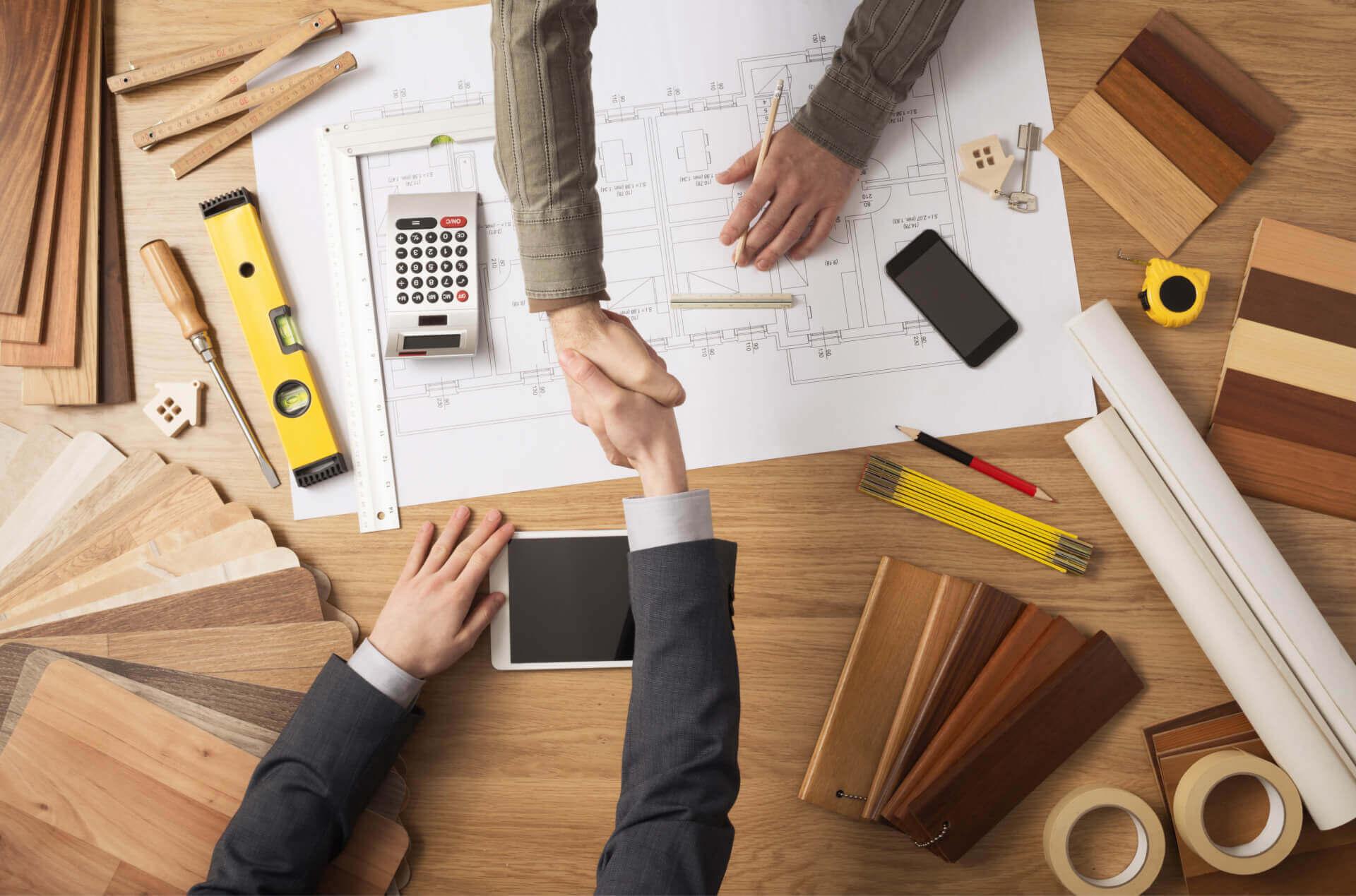 Nasz architekt podaje rękę klientowi, nowoczesne narzędzia budowlane na stole, zdjęcie wyraża gotowość ekip budowlanych do postawienia domu z keramzytu