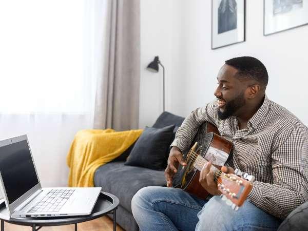 Man having an online guitar lesson