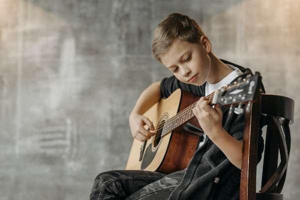 A boy learning guitar
