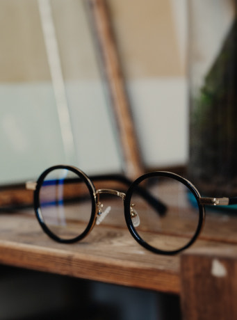A photo of a pair of dark framed glasses sitting on a wooden table. The glasses have a round shape. The background blur is very strong, so they are in focus.