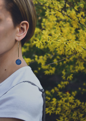 A photo shows a young woman with short hair in. The picture cuts off her face, so only her ear and earring are in focus. In the back, there is a healthy looking bush. The weather seems sunny.