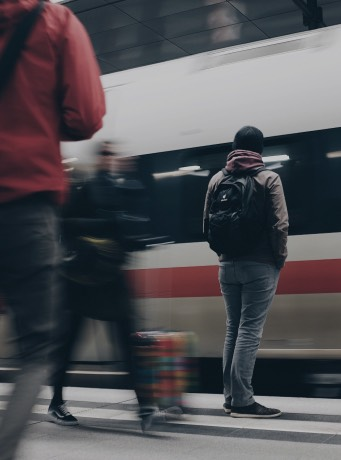 A photo shows a man with a backpack standing at a train station. Directly in front of him, a train is arriving. There are several people moving around him, too, so he appears to be the only stationary object in the picture.