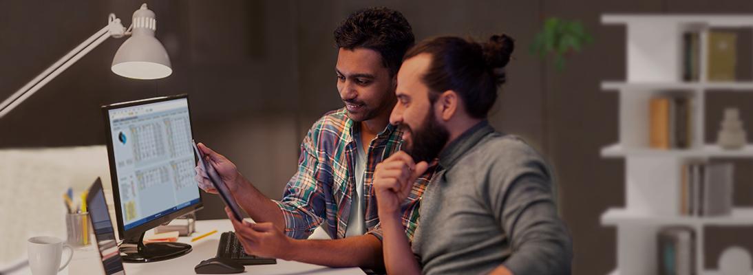 Deux hommes regardent une tablette, en arrière-plan Libelle SABMON fonctionne sur un PC
