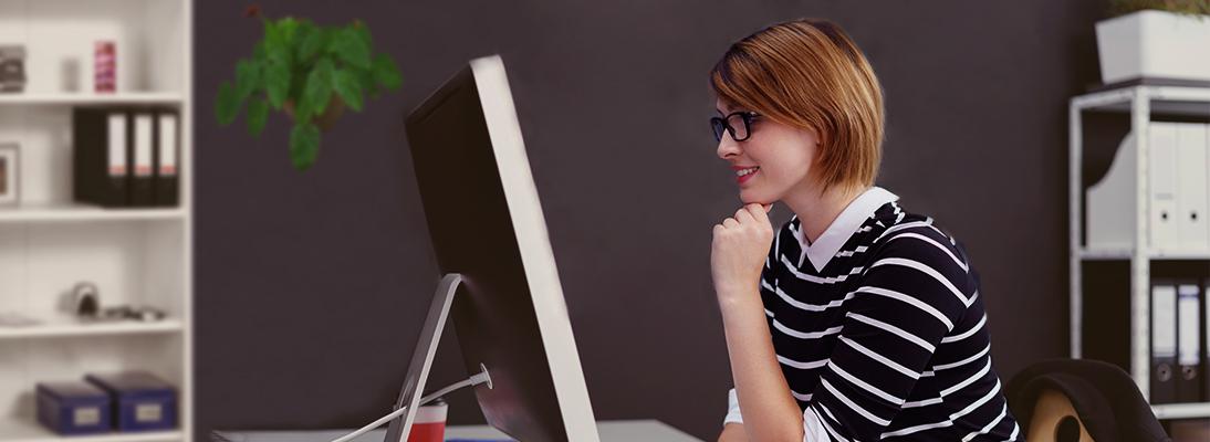 Jeune femme assise devant un écran avec une interface utilisateur par Libelle DataMasking