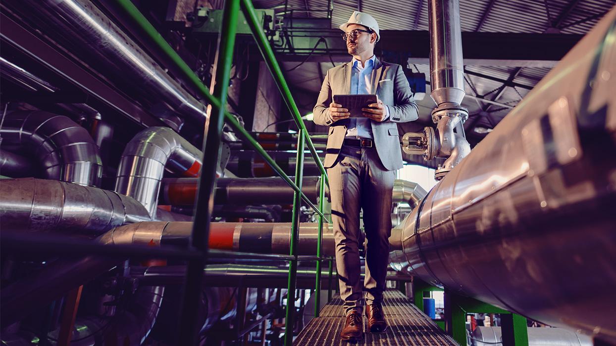 Un homme en costume traverse un bâtiment d'usine avec une tablette