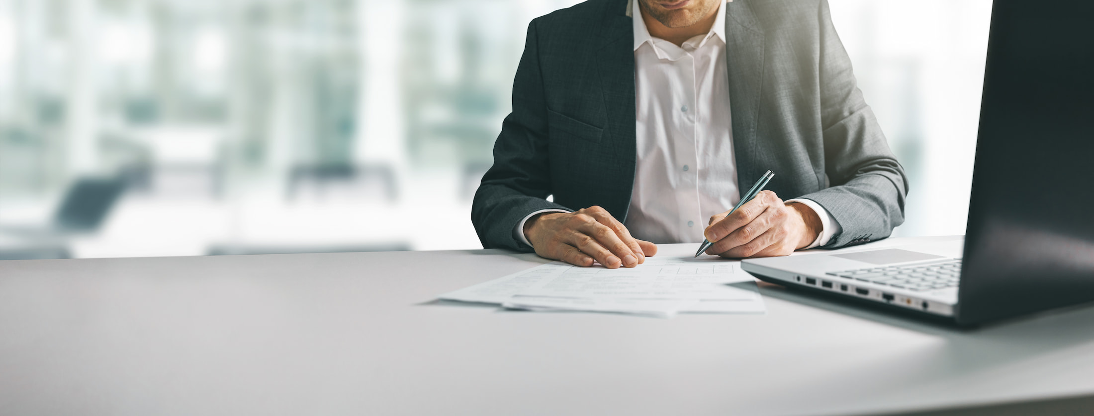 Image of a man signing documents