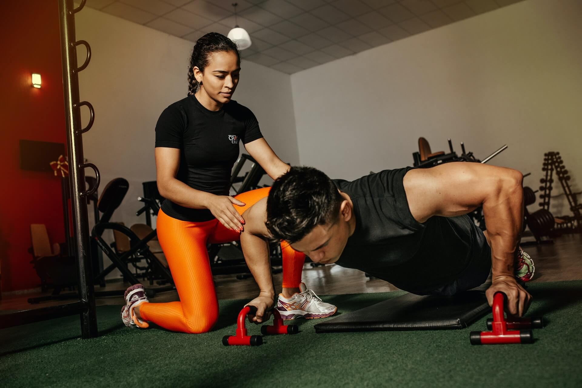 Trainer assisting someone doing pushups
