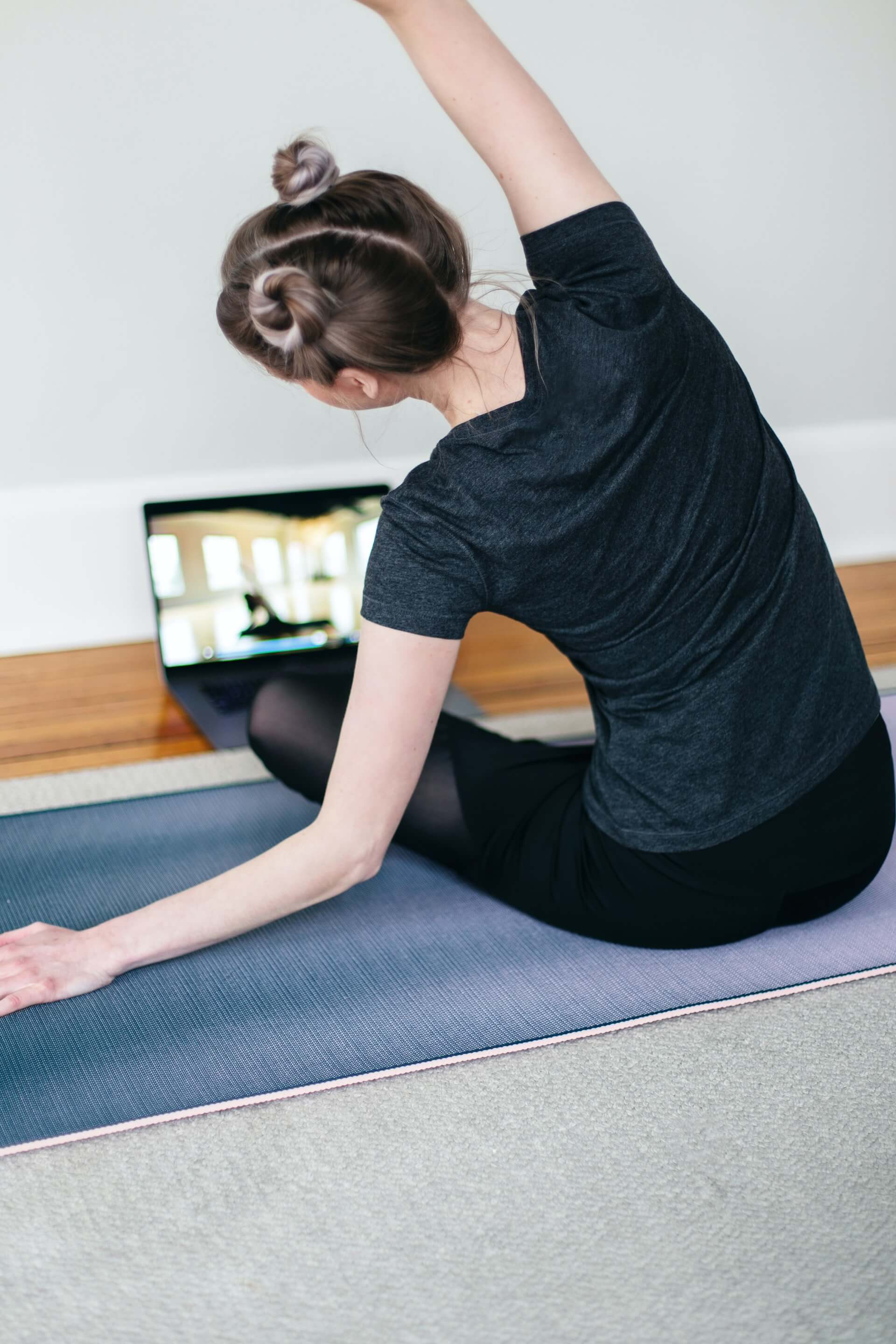 Person attending a yoga session on their laptop